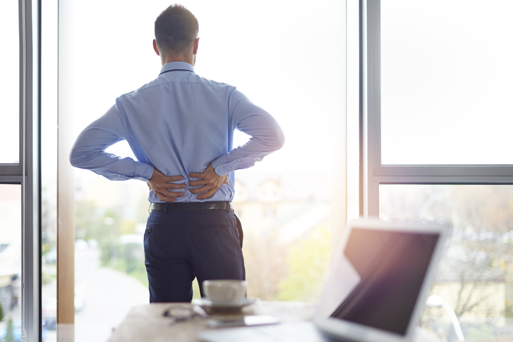 Man in office with low back pain